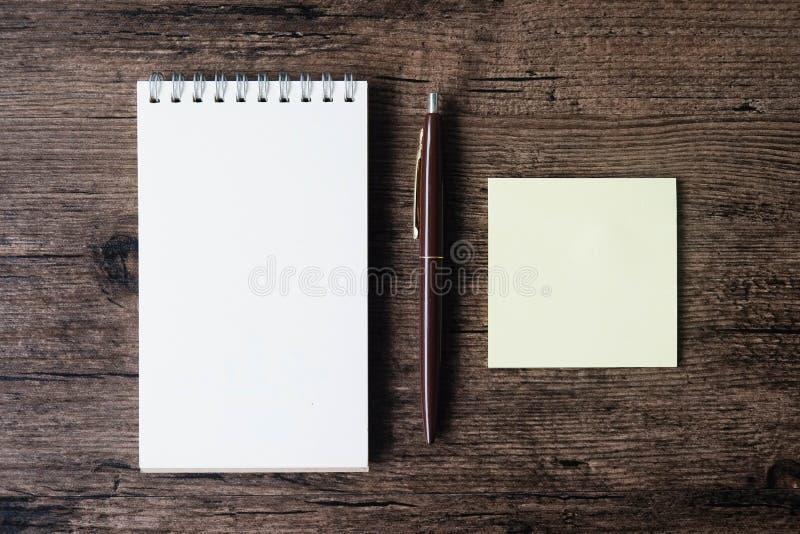 Imagen de la visión superior del cuaderno en blanco, del papel de nota pegajoso vacío y del PE fotos de archivo