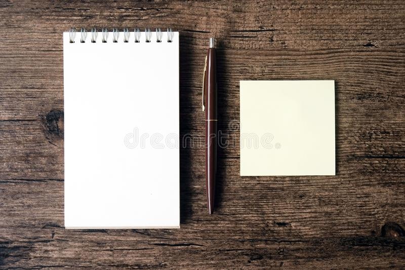 Imagen de la visión superior del cuaderno en blanco, del papel de nota pegajoso vacío y del PE fotografía de archivo libre de regalías