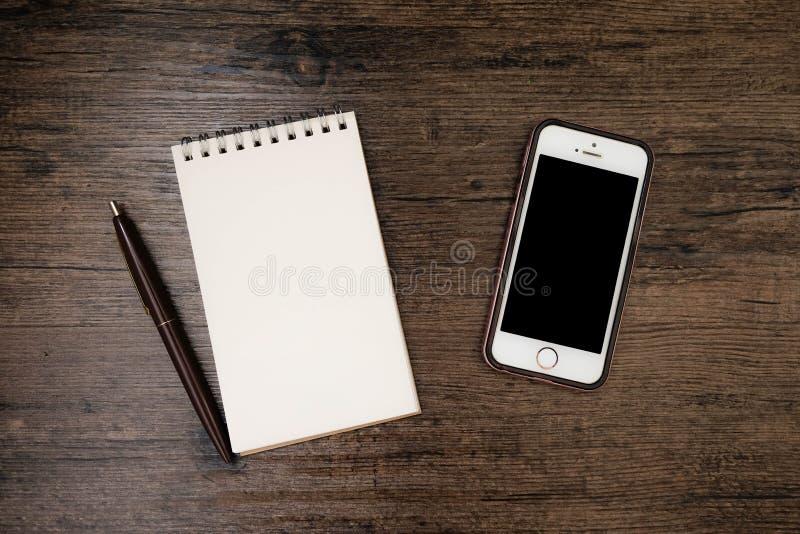 Imagen de la visión superior del cuaderno de la página en blanco con la pluma y del teléfono móvil en la tabla de madera fotos de archivo libres de regalías