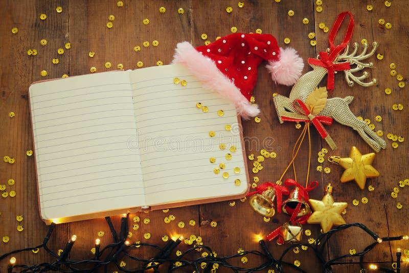 Imagen de la visión superior de las decoraciones festivas de la Navidad al lado del cuaderno abierto vacío en viejo fondo de made fotos de archivo