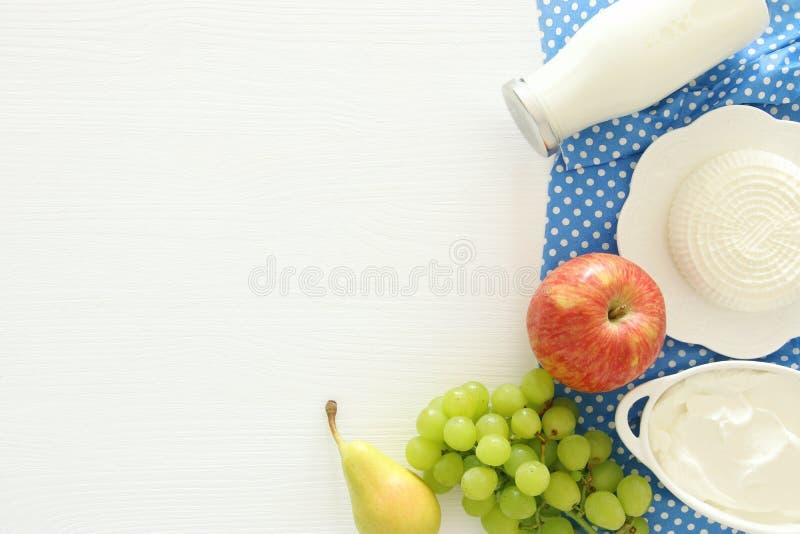 Imagen de la visión superior de los productos lácteos y de las frutas en fondo de madera Símbolos del día de fiesta judío - Shavu imagen de archivo