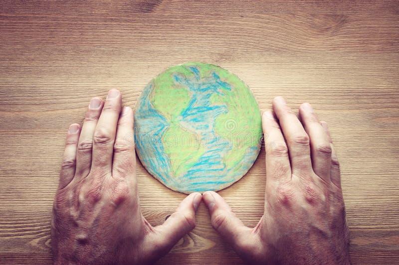 Imagen de la visión superior de la mano del hombre que sostiene el globo de la tierra imagen de archivo libre de regalías