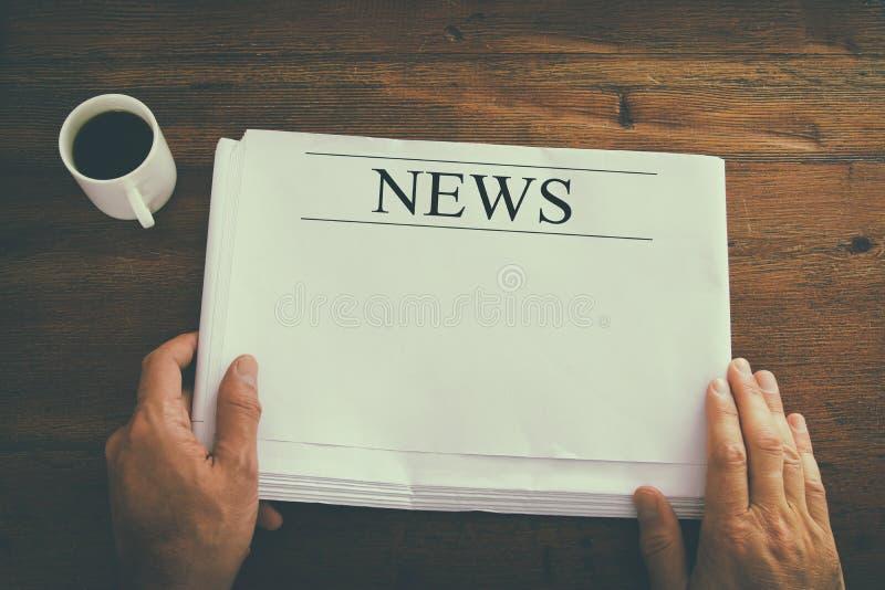 imagen de la visión superior de la mano masculina que sostiene el periódico en blanco con el espacio vacío para añadir noticias o fotografía de archivo libre de regalías