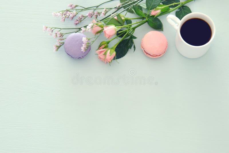 Imagen de la visión superior de la taza blanca de café y de macaron colorido o de los macarrones sobre fondo de madera en colores fotografía de archivo