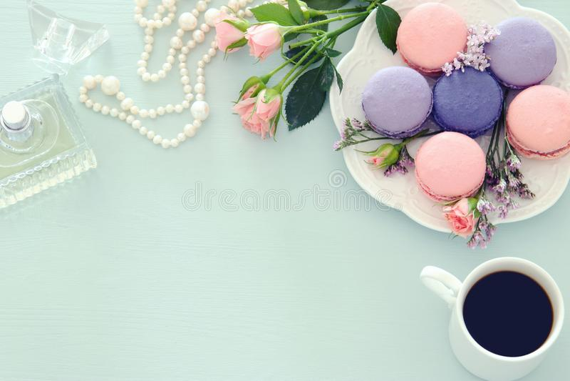 Imagen de la visión superior de la taza de café blanca, perfume, perlas blancas y macaron o macarrones coloridos sobre fondo de m imágenes de archivo libres de regalías