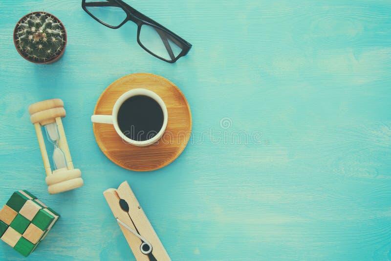 Imagen de la visión superior de la taza de café, vidrios, reloj de arena en la tabla de madera imagenes de archivo