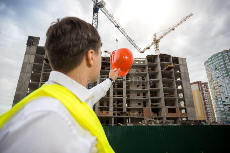 Imagen de la vista posterior del achitect masculino que señala con el casco de protección rojo en el nuevo edificio bajo construc fotos de archivo