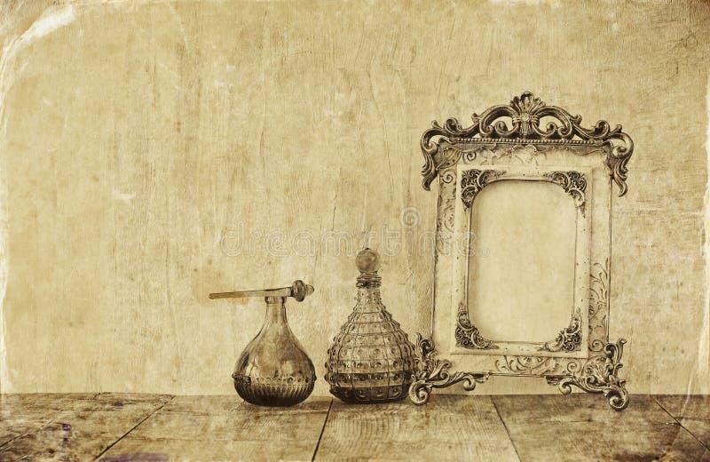 Imagen de las botellas clásicas del marco y de perfume de la antigüedad del vintage del victorian en la tabla de madera Imagen fi stock de ilustración