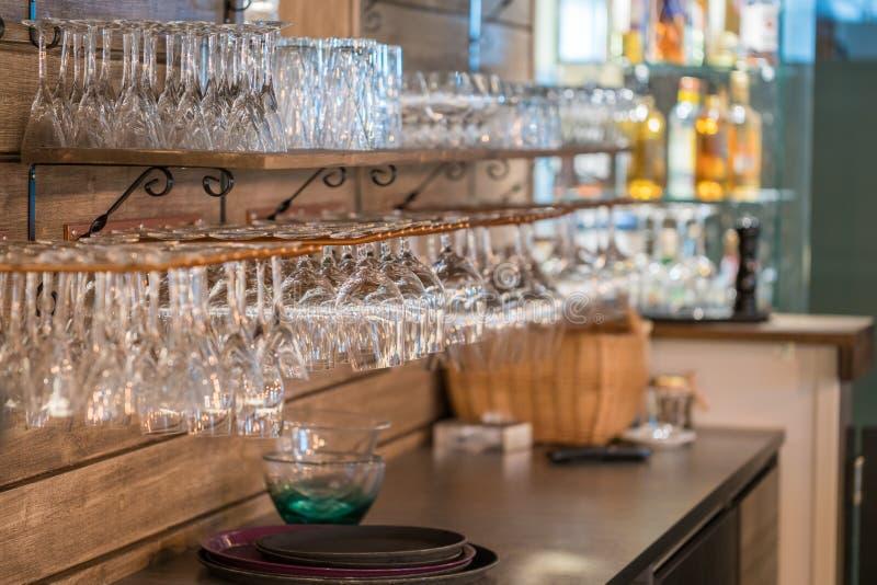 Imagen de las copas de vino apiladas en los estantes de cristal colgantes de la barra del metal negro en una barra, club nocturno fotografía de archivo