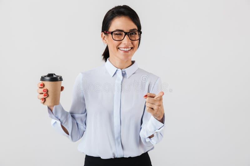 Imagen de las lentes que llevan de la mujer acertada de la secretaria que beben el café de la taza de papel en la oficina, colocá foto de archivo