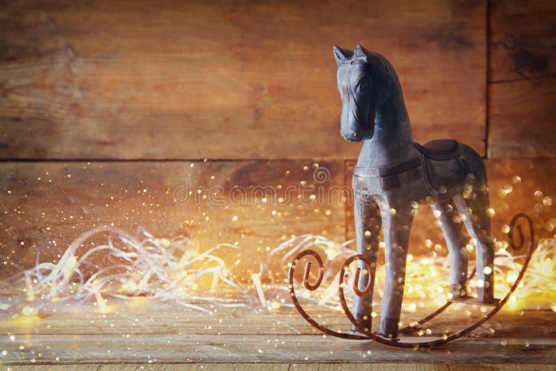 Imagen de las luces del caballo mecedora y de la Navidad de la magia en la tabla de madera foto de archivo libre de regalías