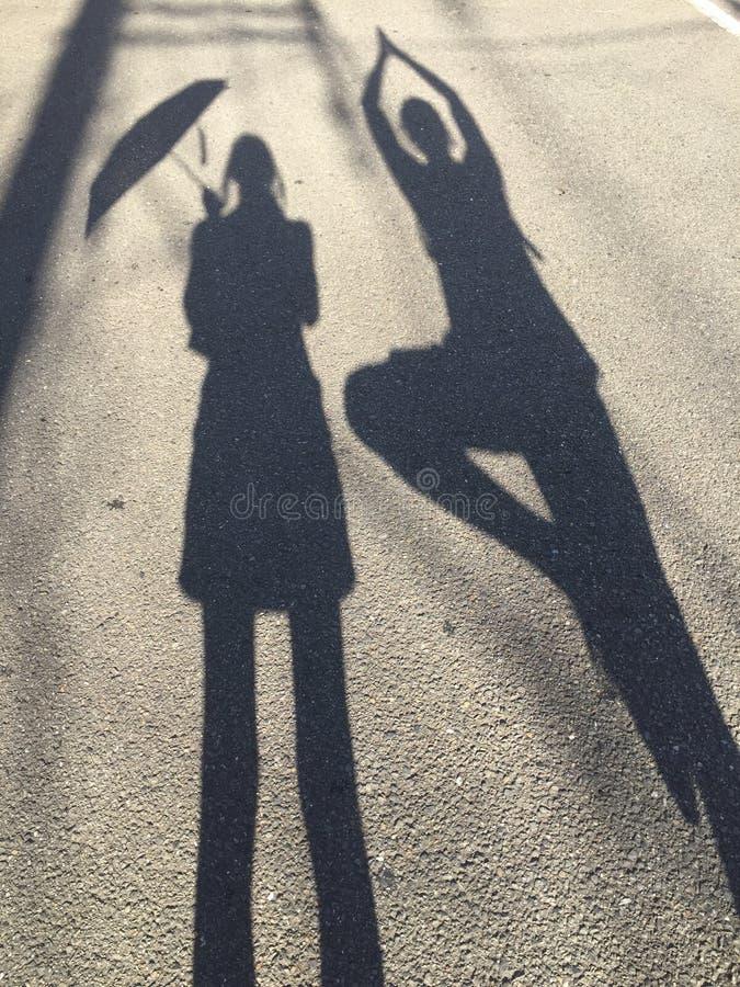 Imagen de las mujeres que detienen un paraguas y a un hombre que hacen la actitud del árbol fotos de archivo libres de regalías