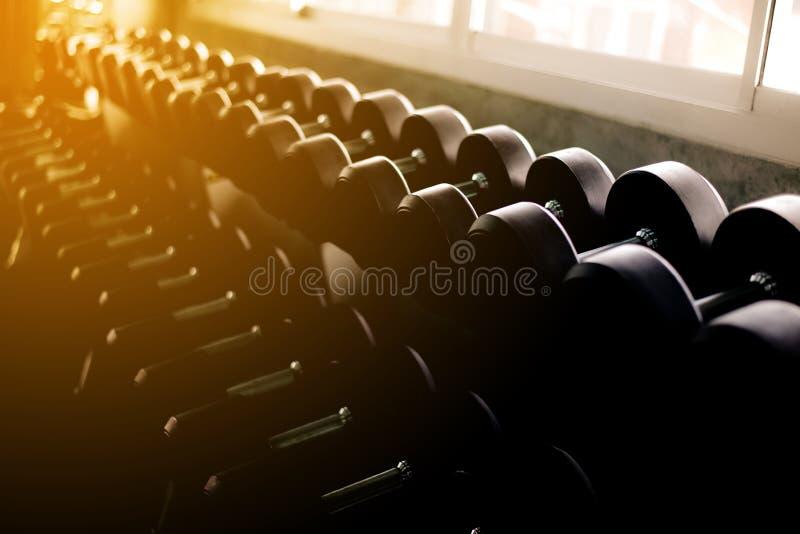 Imagen de las pesas de gimnasia blured instaladas en el centro del gimnasio, entrenamiento en el estante, cierre entonado oscuro  fotos de archivo