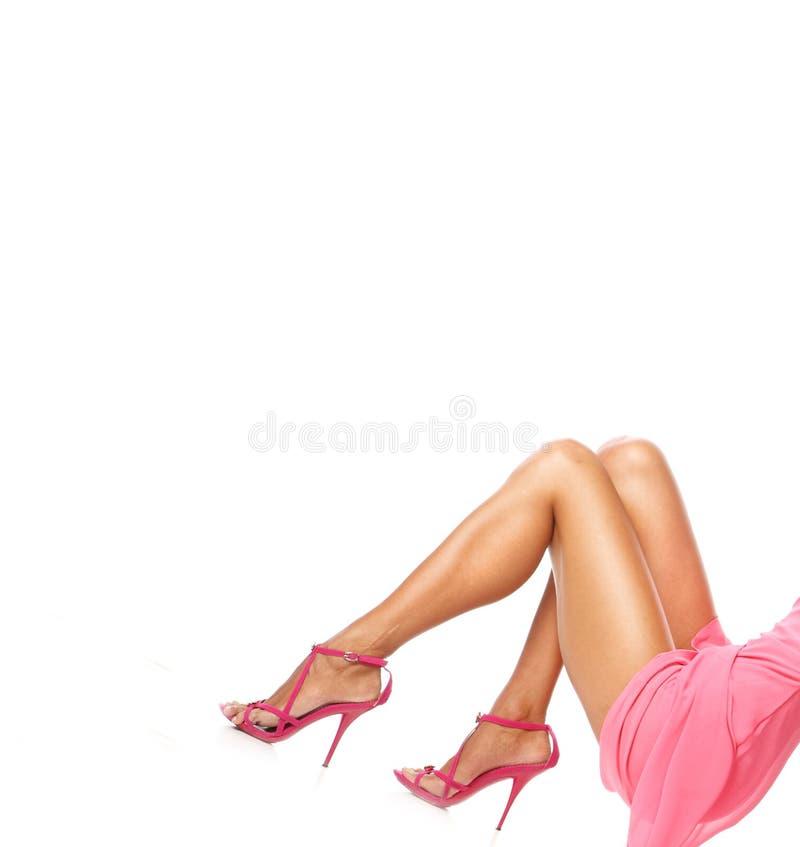 Imagen de las piernas femeninas delgadas que llevan los zapatos elegantes rojos en los tacones altos en el fondo blanco, calzado  imagen de archivo