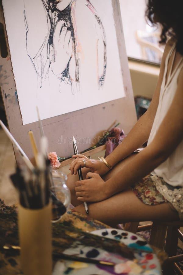 Imagen de las pinturas de la muchacha del artista en lona en estudio fotos de archivo