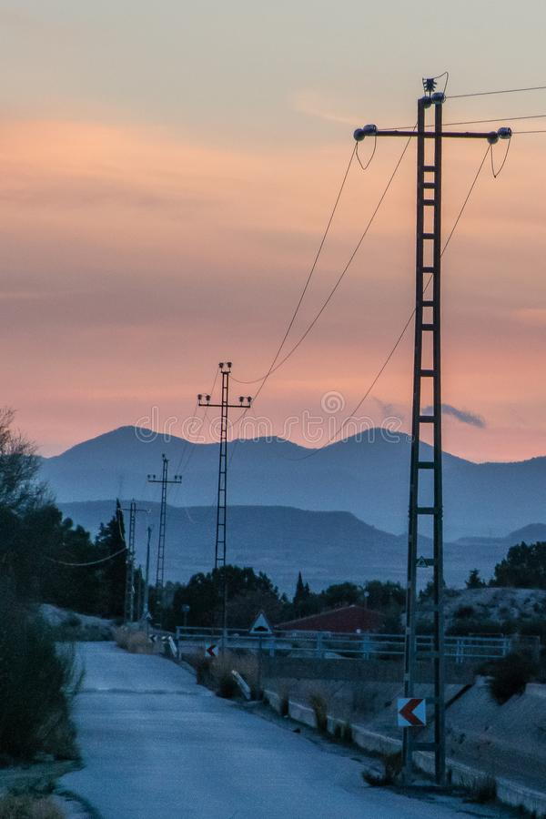 Imagen de las torres de la electricidad en la puesta del sol fotografía de archivo libre de regalías