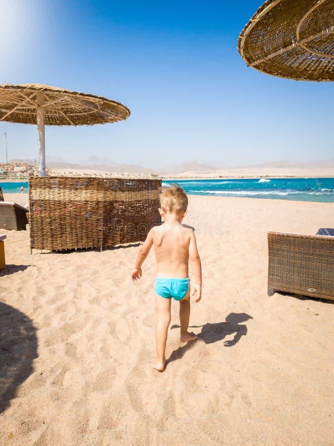 Imagen de los 3 años adorables del niño pequeño que camina en la arena caliente de la playa al mar Niño que relaja y que tiene bu imagen de archivo libre de regalías