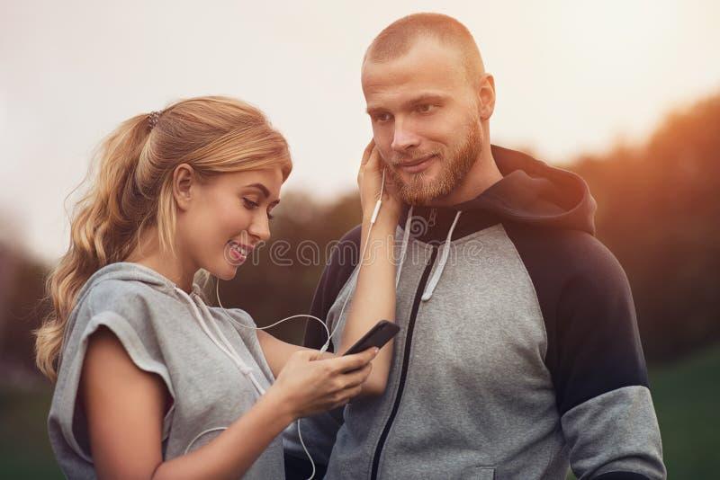 Imagen de los amigos cariñosos de los pares del deporte feliz de la aptitud en música al aire libre que escucha del parque con lo foto de archivo