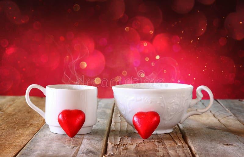 Imagen de los chocolates de la forma del corazón de la remolque y de las tazas rojos de los pares de café en la tabla de madera fotos de archivo