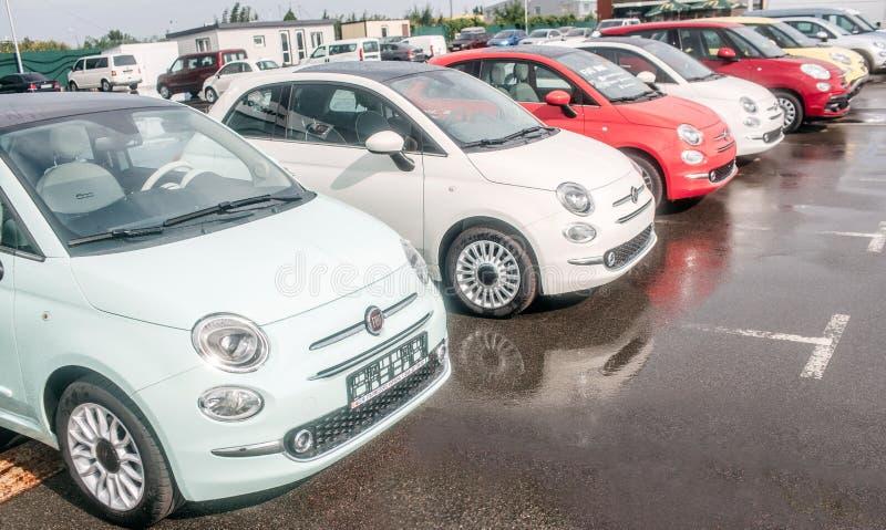 Imagen de los coches pequeños y hermosos de autorización que se colocan afuera en estacionamiento Hay coches rojos y blancos El a foto de archivo libre de regalías
