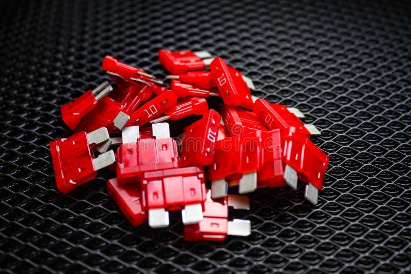Imagen de los fusibles rojos del coche eléctrico para 10 amperios, en un fondo oscuro fotos de archivo libres de regalías