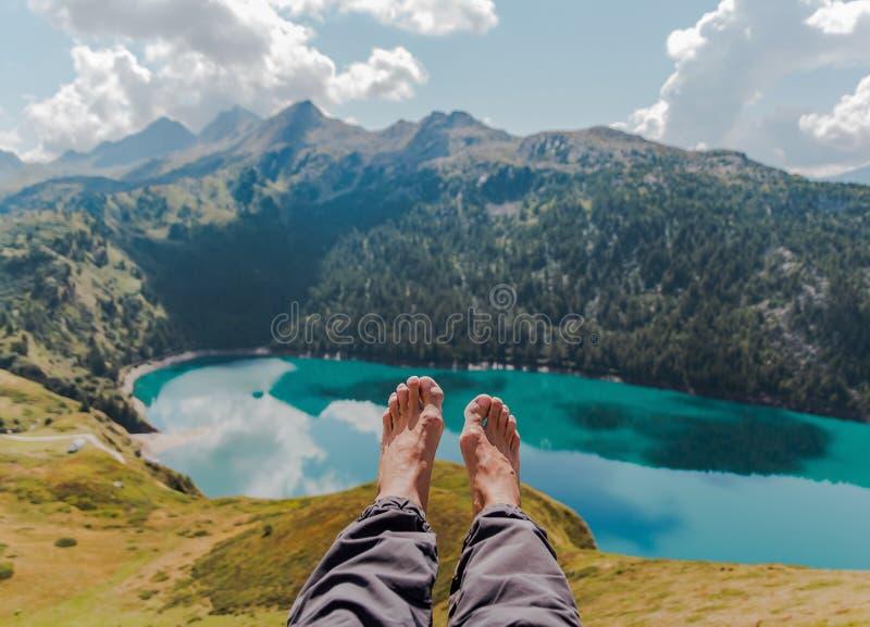 Imagen de los pies y de las piernas con las montañas y del lago masculinos de Ritom como fondo imagenes de archivo