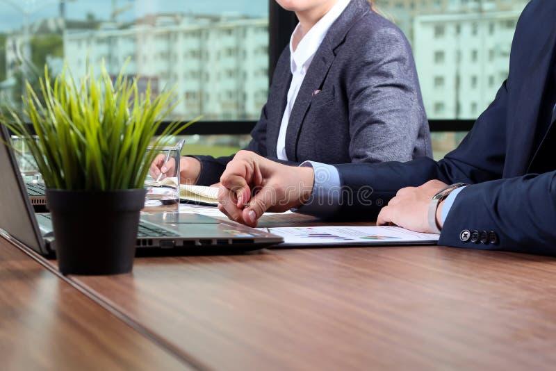 Imagen de los socios comerciales que discuten documentos e ideas en el mee fotos de archivo