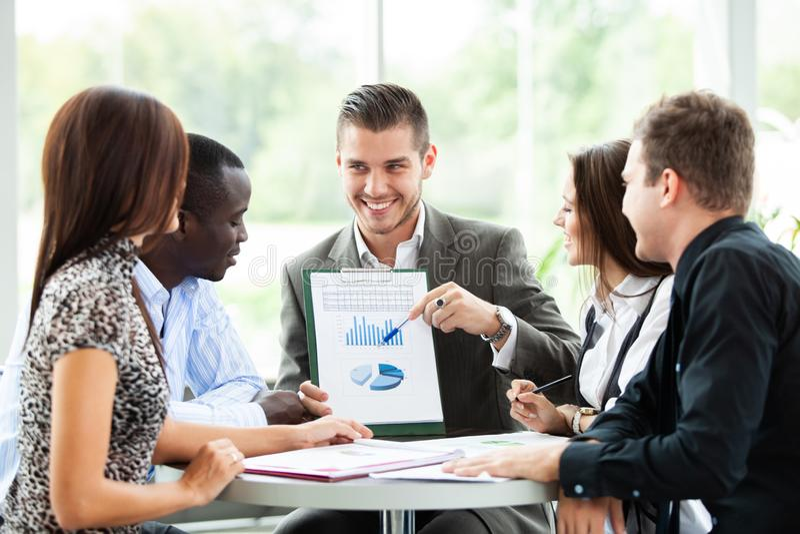 Imagen de los socios comerciales que discuten documentos e ideas en la reunión fotografía de archivo