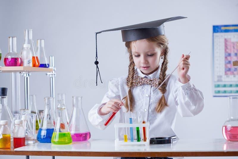 Imagen de los tubos de mezcla de la muchacha elegante en laboratorio fotos de archivo libres de regalías