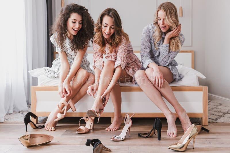 Imagen de los vestidos que llevan elegantes adorables de las muchachas 20s que intentan encendido imágenes de archivo libres de regalías