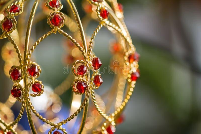 Imagen de macro de la hermosa decoración dorada de Navidad con joyas rojas y bokeh escénico fotos de archivo libres de regalías