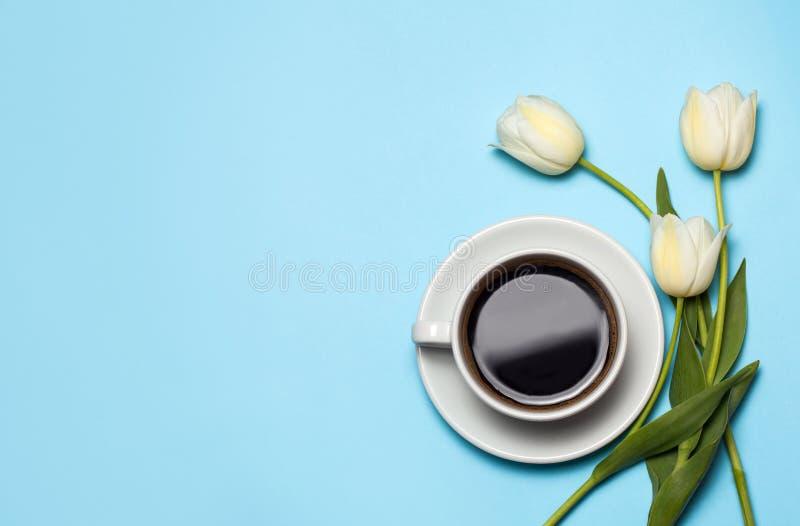 Imagen de Minimalistc de la taza de café y de tulipanes blancos en fondo azul Concepto del café de la primavera Visión superior,  fotos de archivo