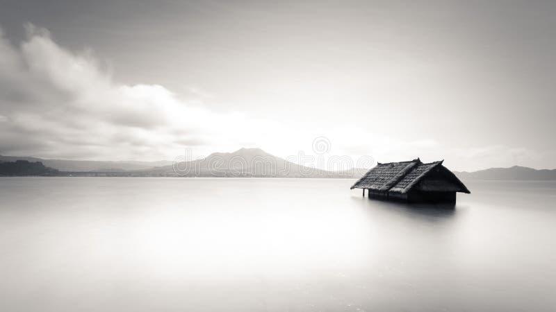 Imagen de Minimalistic de la casa abandonada que flota en el agua foto de archivo
