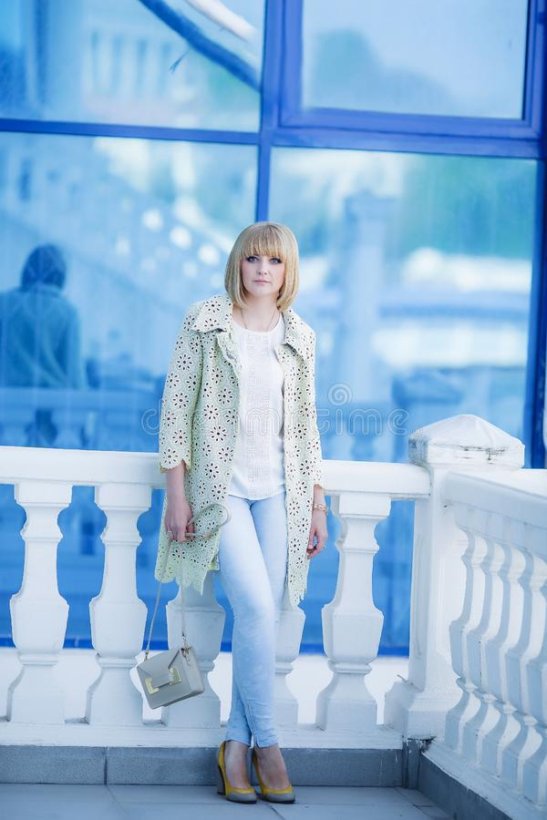 Imagen de moda del otoño de la mujer joven linda con los pelos cortos y sonrisa sincera Capa de moda, vaqueros del dril de algodó foto de archivo
