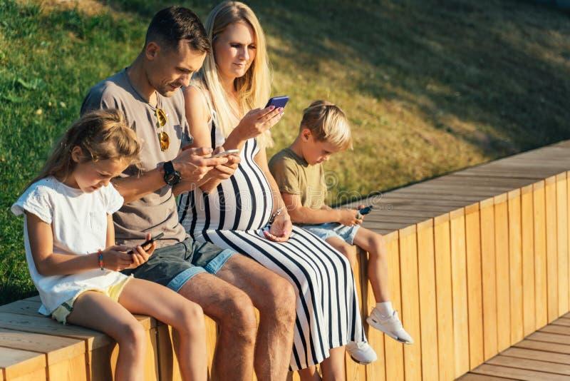 Imagen de padres con la hija y el hijo que se sientan en la cerca de madera con los teléfonos en manos fotografía de archivo libre de regalías