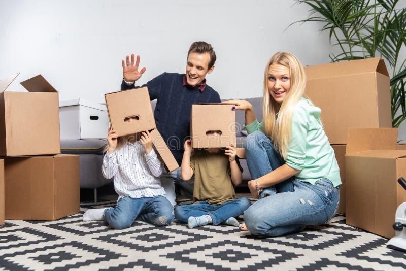 Imagen de padres y de niños con las cajas de cartón en sus cabezas en el nuevo apartamento imágenes de archivo libres de regalías