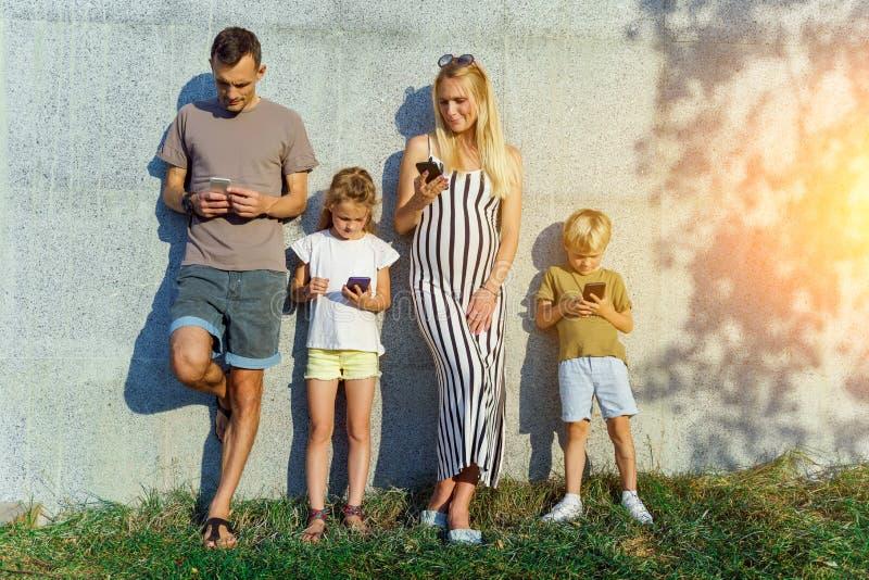 Imagen de padres y de niños con los teléfonos en sus manos que se colocan en el muro de cemento en la calle foto de archivo