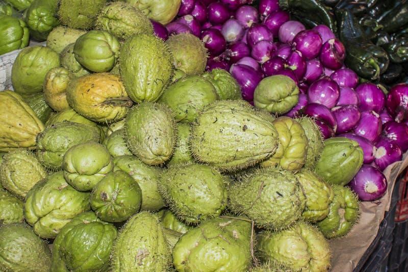 Imagen de productos frescos en cebollas mexicanas, chiles y chayotes de un mercado fotografía de archivo