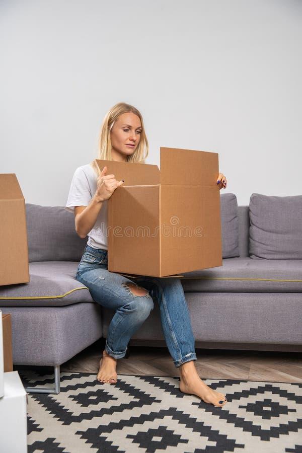 Imagen de rubio joven con la caja de cartón que se sienta en el sofá fotos de archivo libres de regalías