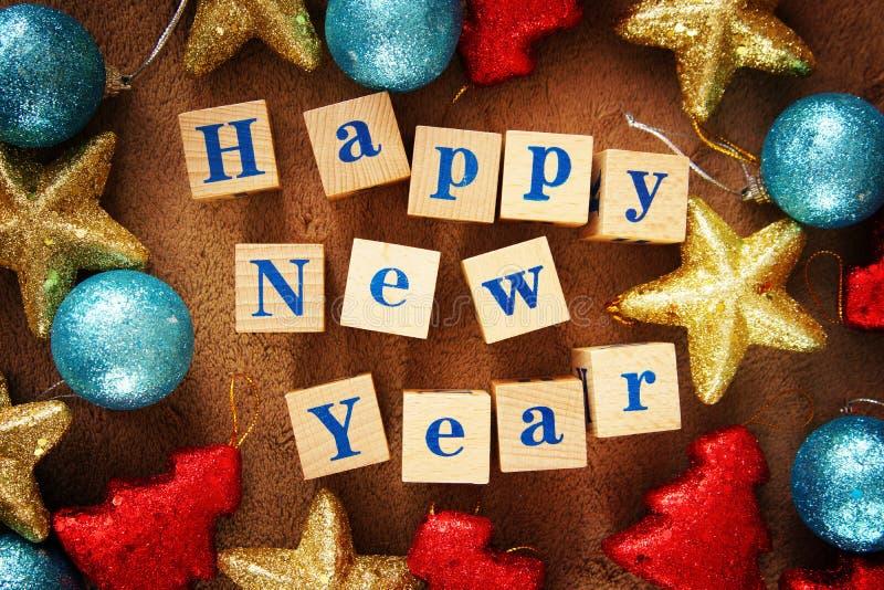 Imagen de saludo festiva del Año Nuevo con un texto en los cubos de madera y las decoraciones coloridas imagen de archivo libre de regalías