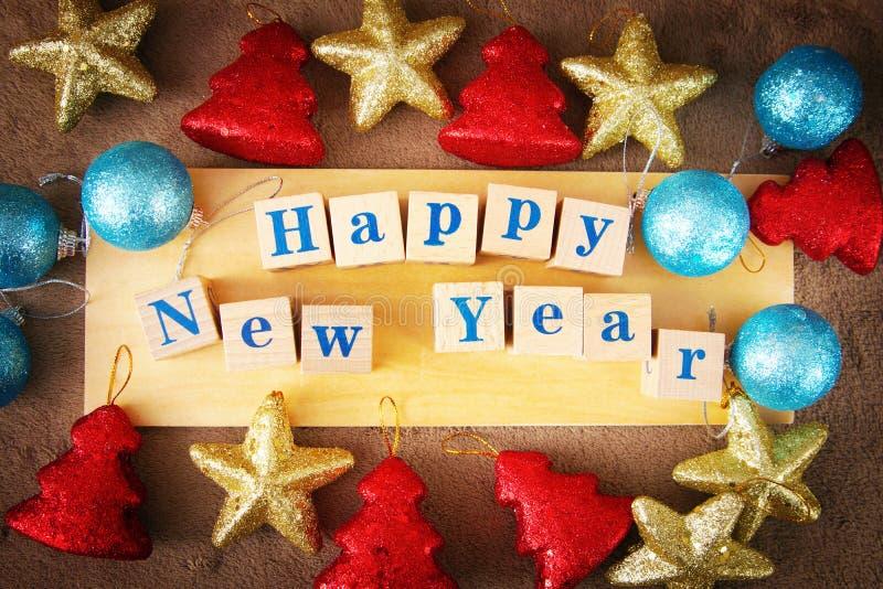 Imagen de saludo festiva de la Feliz Año Nuevo con un texto en los cubos de madera y los juguetes coloridos imágenes de archivo libres de regalías