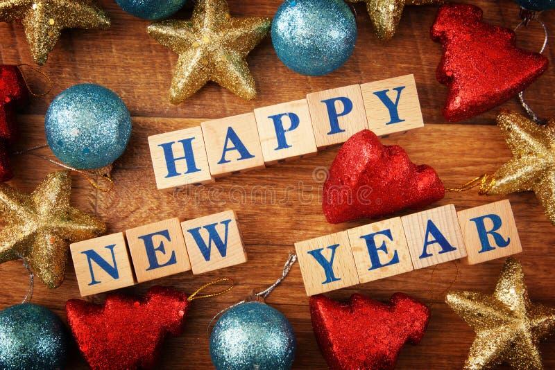 Imagen de saludo festiva de la Feliz Año Nuevo con un texto en los cubos de madera y los juguetes coloridos brillantes imagen de archivo libre de regalías