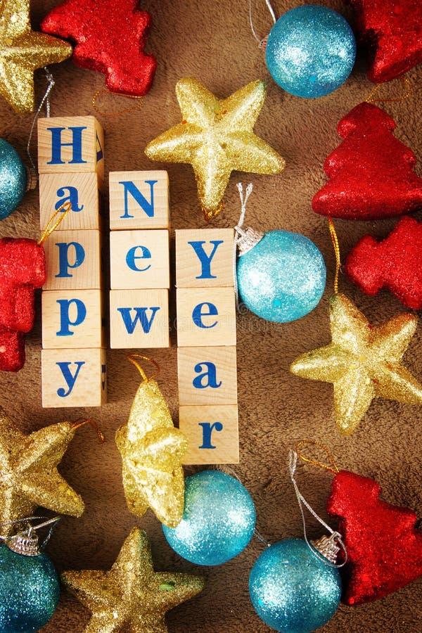 Imagen de saludo festiva viva de la Feliz Año Nuevo con un texto en los cubos de madera y las decoraciones coloridas imágenes de archivo libres de regalías