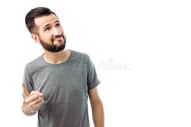 Imagen de un hombre sonriente que se coloca en un fondo blanco que tiene una idea El concepto de gestos El individuo barbudo herm fotografía de archivo