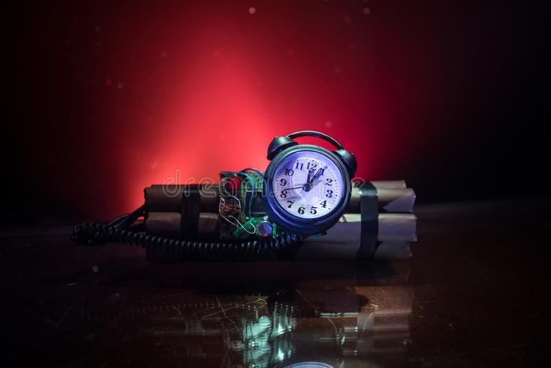 Imagen de una bomba de relojería contra fondo oscuro Contador de tiempo que cuenta abajo a la detonación iluminada en una luz del imagen de archivo