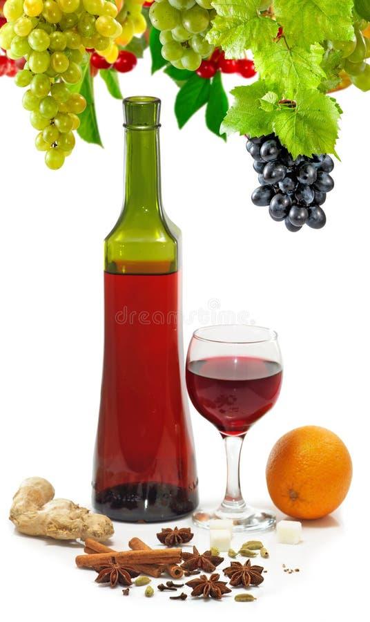imagen de una botella de vino, de un vidrio de vino, de uva, de naranja y de primer de las especias imagen de archivo