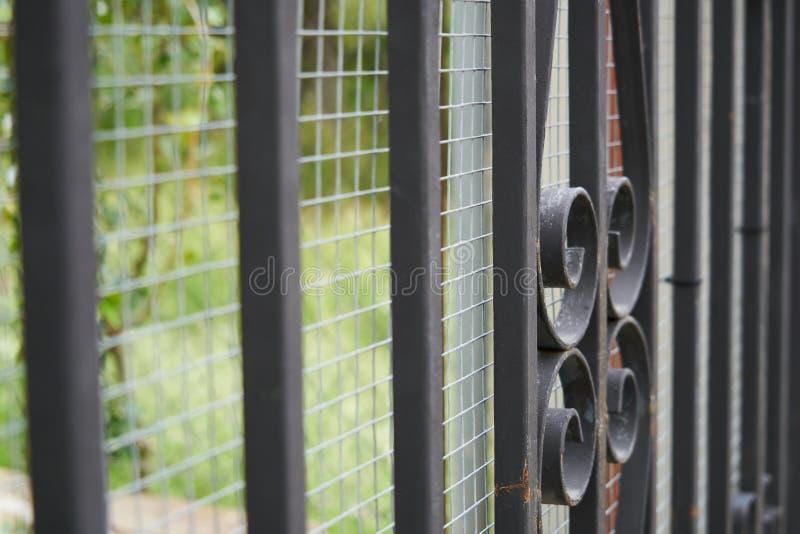 Imagen de una cerca labrada decorativa hermosa del arrabio con la forja art?stica Cierre de la barandilla del metal para arriba fotografía de archivo