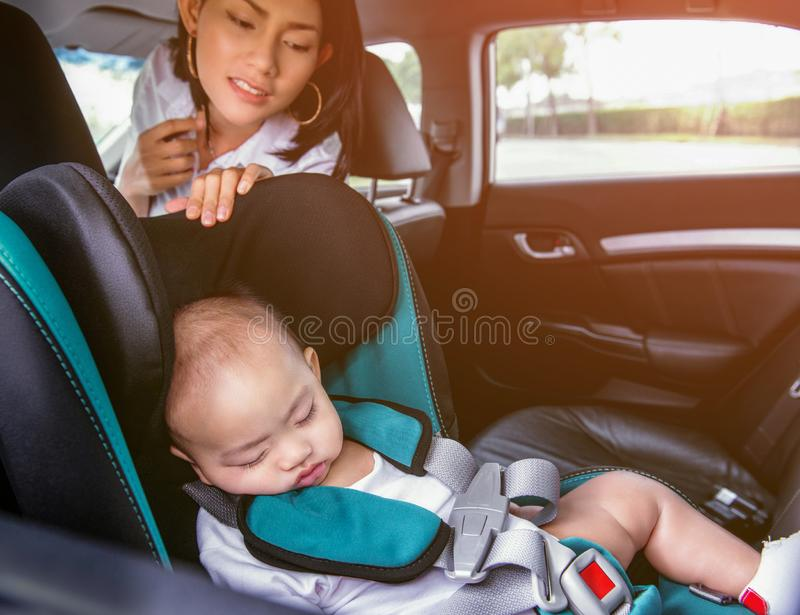 Imagen de una madre asiática que mira a su hijo el dormir en el asiento de carro fotografía de archivo libre de regalías