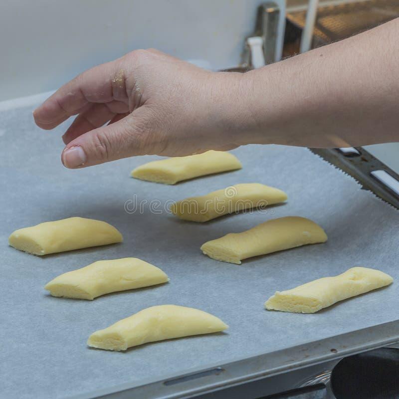 Imagen de una mano de una mujer que coloca las galletas crudas en un papel encerado en una hornada fotos de archivo