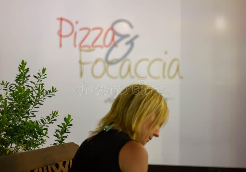 Imagen de una mujer con el fondo con una pared con la pizza y el focaccia de la palabra fotografía de archivo
